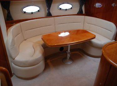 Салон с мягким кожаным диваном и столом на яхте Princess V42 - Yachts.ua