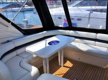 Белый кожаный диван со столом на верхней палубе яхты Princess V42 - Yachts.ua